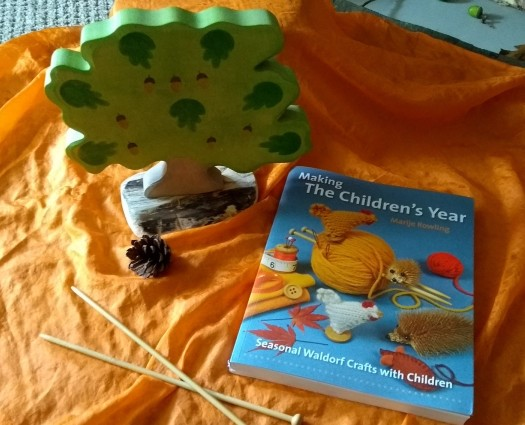 image shows making the children's year book, knitting needles, toy tree, pinecone